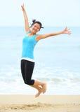 Азиатская женщина скача на пляж Стоковые Изображения