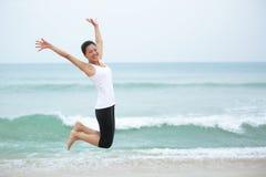 Азиатская женщина скачет на пляж. Стоковые Фотографии RF