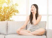 Азиатская женщина смеясь над на телефоне Стоковое Изображение
