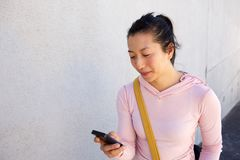Азиатская женщина смотря мобильный телефон outdoors Стоковая Фотография RF