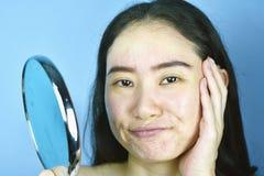 Азиатская женщина смотря, что себя в зеркале, женское чувство надоесть об ее шоу возникновения отражения старея уход за лицом стоковые изображения