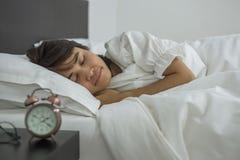 Азиатская женщина спать в кровати, молодой женский лежать в интерьере спальни на ноче стоковые фотографии rf