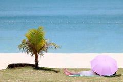 Азиатская женщина спать под тенью зонтика на пляже Стоковые Фотографии RF