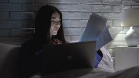 Азиатская женщина спеша для того чтобы закончить отчет о работы поздно в спальне, отсутствующем крайнем сроке сток-видео