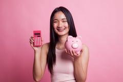 Азиатская женщина с калькулятором и копилкой Стоковое Изображение RF