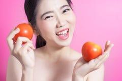 Азиатская женщина с концепцией томата Она усмехаясь и держа томат Сторона красоты и естественный состав Изолировано над розовой п Стоковые Изображения