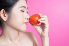 Азиатская женщина с концепцией томата Она усмехаясь и держа томат Сторона красоты и естественный состав Изолировано над розовой п Стоковая Фотография RF
