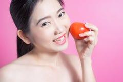 Азиатская женщина с концепцией томата Она усмехаясь и держа томат Сторона красоты и естественный состав Изолировано над розовой п Стоковые Фото