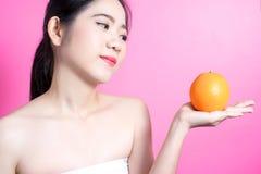 Азиатская женщина с оранжевой концепцией Она усмехаясь и держа апельсин Сторона красоты и естественный состав Изолировано над роз Стоковая Фотография