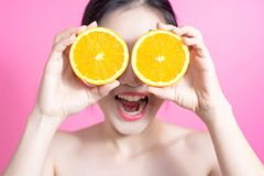 Азиатская женщина с оранжевой концепцией Она усмехаясь и держа апельсин Сторона красоты и естественный состав Изолировано над роз Стоковое Изображение