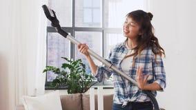 Азиатская женщина с пылесосом имея потеху дома видеоматериал