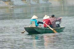 Азиатская женщина с соломенной шляпой в шлюпке Стоковое фото RF