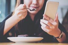Азиатская женщина с удерживанием и использованием стороны smiley умного телефона пока ел пирожное на деревянном столе Стоковая Фотография RF