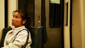 Азиатская женщина с уставшим взглядом в белой sportive рубашке сидит в двигая поезде акции видеоматериалы