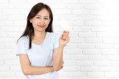 Азиатская женщина усмехаясь держащ карточку Стоковое Изображение RF