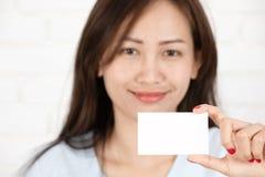 Азиатская женщина усмехаясь держащ карточку Стоковое Изображение