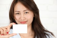 Азиатская женщина усмехаясь держащ карточку Стоковая Фотография