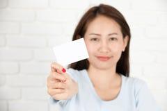 Азиатская женщина усмехаясь держащ карточку Стоковые Изображения