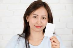Азиатская женщина усмехаясь держащ карточку Стоковое фото RF