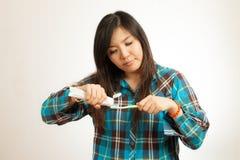 Азиатская женщина чистя ее зубы щеткой Стоковые Фото