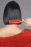 Азиатская женщина чистя ее короткие волос щеткой стоковые изображения