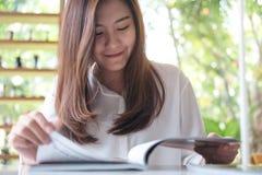 Азиатская женщина читая книгу в белом современном кафе с зеленой предпосылкой природы Стоковое Изображение