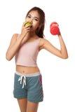 Азиатская здоровая разминка девушки с гантелью ест яблоко Стоковые Изображения RF