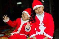 Азиатская индийская этничность 2 ягнится нося иметь шляпы Санты развевая Стоковая Фотография RF