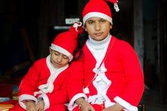 Азиатская индийская этничность 2 ягнится нося иметь шляпы Санты развевая Стоковое Изображение RF