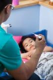 Азиатская лихорадка острословия девушки в кровати стоковые фото