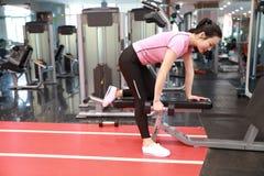 Азиатская китайская женщина в маленькой девочке ŒFitness ¼ ï спортзала в спортзале делая тренировки с гантелями Стоковая Фотография RF