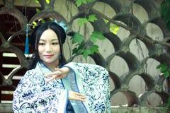 Азиатская китайская женщина в традиционном голубом и белом платье Hanfu, игре в известном саде около стены Стоковые Фото