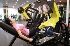 Азиатская китайская женщина в тренировке женщины спорта ŒFitness ¼ ï спортзала прочности ноги в спортзале Стоковое Изображение