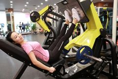 Азиатская китайская женщина в тренировке женщины спорта ŒFitness ¼ ï спортзала прочности ноги в спортзале Стоковые Фото