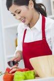 Азиатская китайская женщина подготавливая еду салата овощей в кухне Стоковые Фото