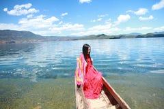 Азиатская китайская красота в красном платье с красным scraf на голове, сидит в каное Mosuo специальном на озере Юньнань Lugu, на Стоковые Фотографии RF