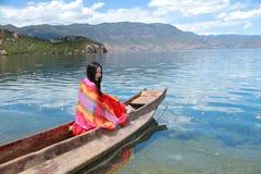 Азиатская китайская красота в красном платье с красным scraf на голове, сидит в каное Mosuo специальном на озере Юньнань Lugu, на Стоковая Фотография RF