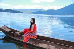 Азиатская китайская красота в красном платье с красным scraf на голове, сидит в каное Mosuo специальном на озере Юньнань Lugu, на Стоковое Фото