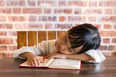 Азиатская китайская маленькая девочка спать на таблице пока делающ домашнюю работу Стоковые Фотографии RF