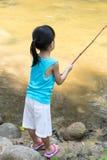 Азиатская китайская маленькая девочка двигая под углом с рыболовной удочкой Стоковая Фотография