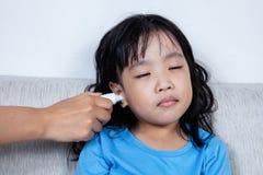 Азиатская китайская маленькая девочка получая измерение уха для temp лихорадки Стоковые Фото