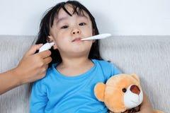 Азиатская китайская маленькая девочка получая измерение уха для temp лихорадки Стоковая Фотография RF