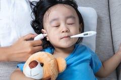 Азиатская китайская маленькая девочка получая измерение уха для temp лихорадки Стоковые Изображения