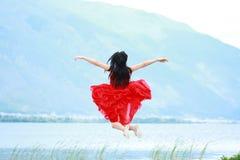 Азиатская китайская маленькая девочка скачет пляжем, наслаждается мирной жизнью Стоковые Изображения
