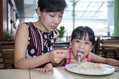 Азиатская китайские мать и дочь есть спагетти bolognese Стоковые Изображения RF
