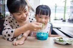 Азиатская китайские мать и дочь есть лапши говядины Стоковое Изображение RF