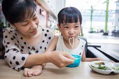 Азиатская китайские мать и дочь есть лапши говядины Стоковые Фотографии RF