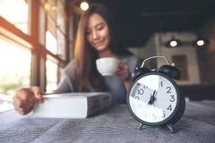 Азиатская книга чтения женщины и выпивая кофе в утре с черным будильником на таблице Стоковые Фотографии RF