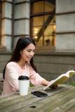 Азиатская книга чтения женщины на кафе Стоковая Фотография