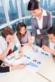 Азиатская команда дела обсуждая диаграммы Стоковые Изображения RF